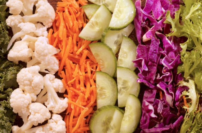 Closeup of precut vegetables including carrots cabbage cauliflower lettuce