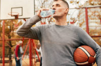 Man drinking water during break in basketball pickup game