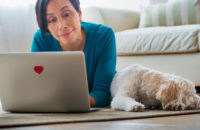 woman relaxing with dog while looking at laptop decorated with a heart