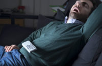 Overweight man with diabetes snoring in front of TV