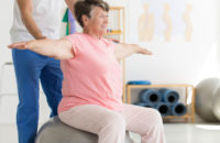 Elderly woman practicing balance with physical therapist providing support