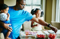 Man serving a healthy breakfast to his two children