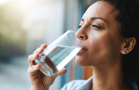 woman taking a drink of water to improve the taste in her mouth