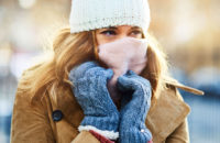 Woman dressed for the cold weather in hat, scarf over face, gloves and coat