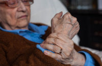 Elderly woman massaging arthritic wrist