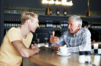 Father and son talking over coffee at a cafe