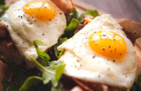 Fried eggs sunny side up, ham and arugula