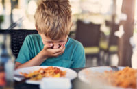 Little boy getting sick at restaurant due to allergic reaction