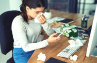 Woman sitting at computer wiping nose and surrounded by used tissues