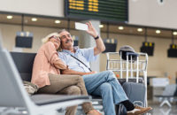 Older couple taking selfie at airport
