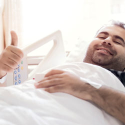 Man in hospital bed after organ donation - thumbs up