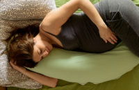 Pregnant woman sleeping on side with maternity pillow