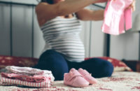 Pregnant woman sitting on bed sorting through baby clothes