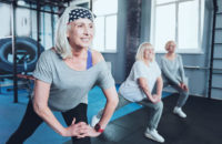 Older women performing lunges during exercise class