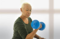 Elderly woman uses weights for strength training at home