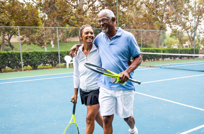 Active elderly couple exiting tennis court