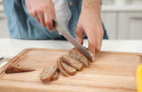 woman slicing healthy bread with nuts