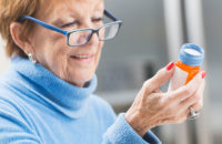 Woman reading her medication bottle