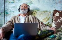 Older man happily relaxing and listening to music