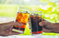 Two glasses of soda on a bright background