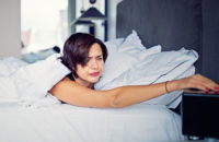Tired woman turning off bedside alarm clock