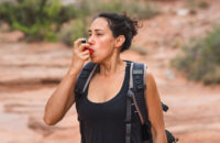 Woman uses inhaler during hike