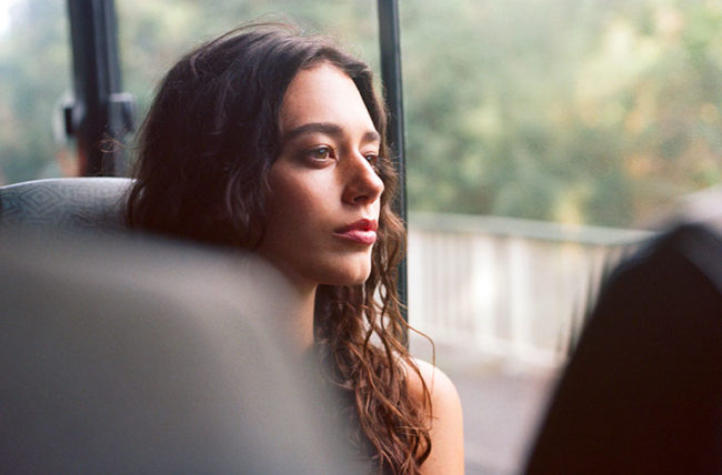 A young woman stares serenely out the window