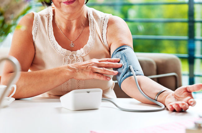 Older woman taking her blood pressure at home