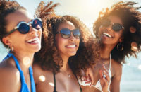 3 dark-skinned women laughing at the beach