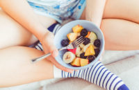 Woman eating bowl of mixed fruits for snack
