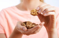 Woman eating walnuts from her hand