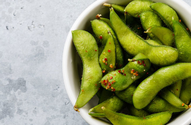 Cooked edamame in a white bowl