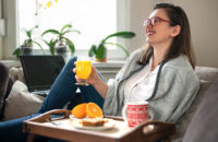 Woman eating healthy breakfast with eggs, oranges and tea