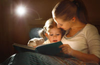 Mother reading book to daughter at bedtime