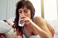 Woman taking medication while in bed
