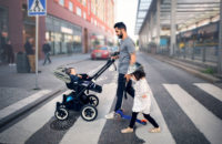 Father on walk with baby in stroller and young daughter