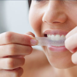 Woman using teeth whitening strip