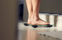 Woman stepping on scale in bathroom