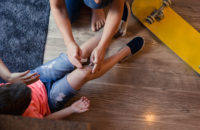 Mom applying bandaid to child's knee after accident