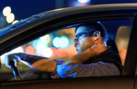 Man rubbing neck while driving car at night in traffic