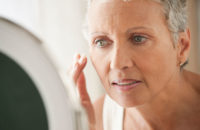 Older woman looking at skin condition in mirror