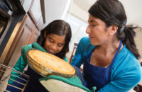Mother a daughter remove pie from hot kitchen oven