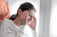 Woman with migraine headache on airplane