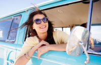 Woman hanging out a car window wearing polarized sunglasses