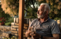 Older man deep in thought on porch at early evening