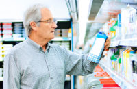 Elderly man checking food labels for sodium at grocery store