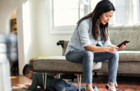 Woman sitting in living room wearing skinny jeans while son plays underfoot