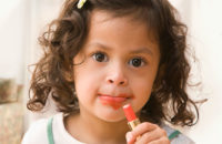 Little girl playing with lipstick