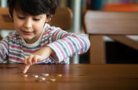 Child picking up coin from table