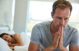 Man upset sitting on edge of bed with woman in background